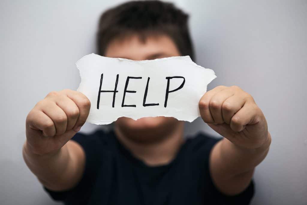 chico con un cartel de help o ayuda