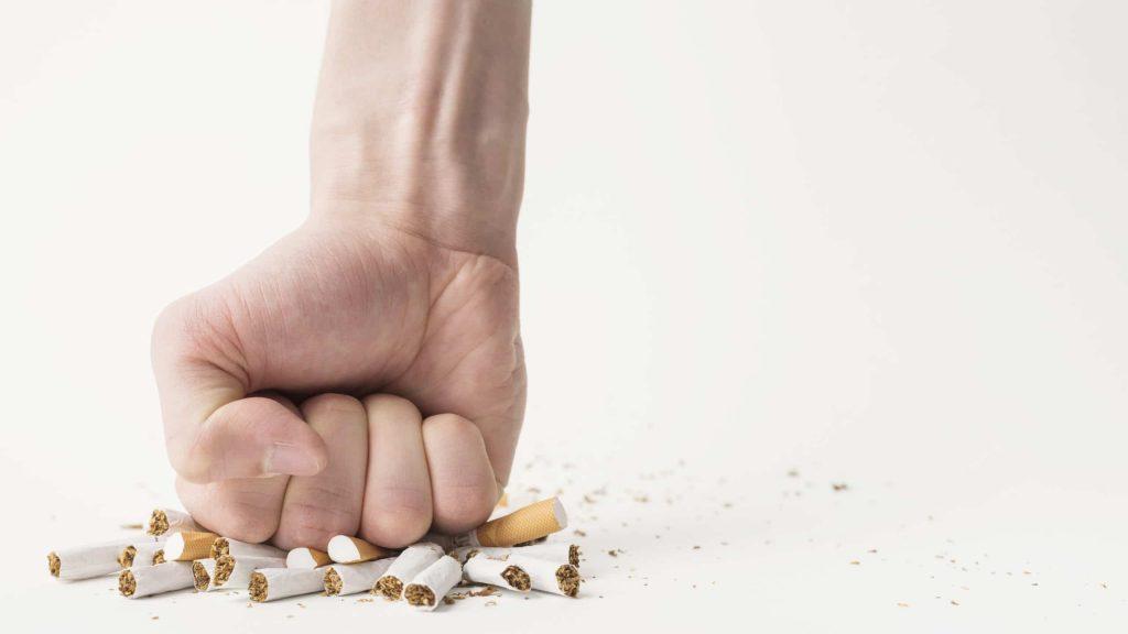 puño cerrando rompiendo cigarrillos